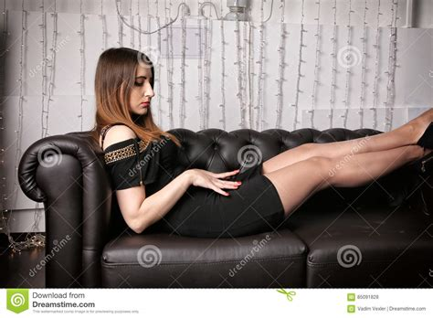 sit your y ass on that couch young woman in dress and heels sitting on a black leather