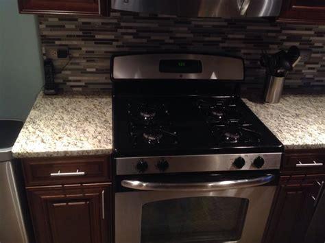 giallo ornamental light granite Kitchen with Cabinetry
