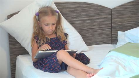 working girls in bed toddler girl sitting on a potty and reading book stock