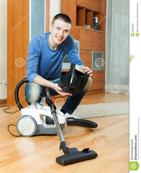 Vacuum The Living Room In Vacuuming With Vacuum Cleaner On Parquet Floor In