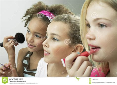 portrait of teenage girl putting lipstick on while looking at her girls putting on makeup and lipgloss stock photo image