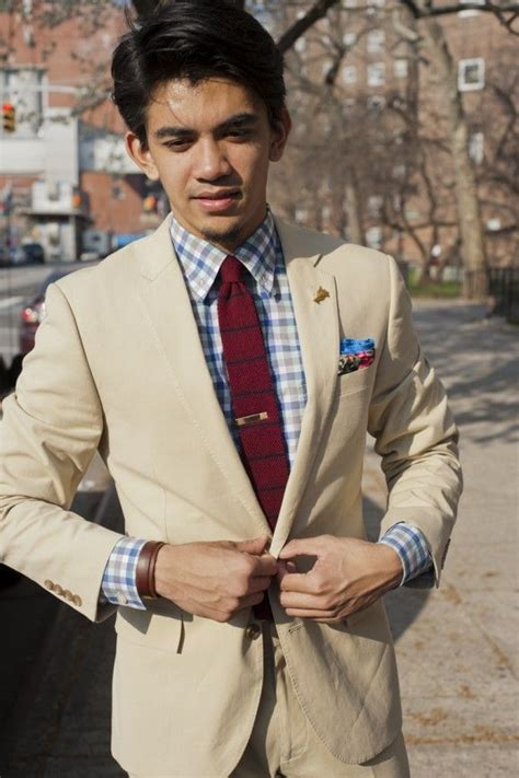 striped tie and checkered shirt beneath an elegant grey tan suit plaid shirt red knit tie with blue stripes