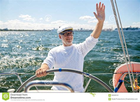 sailing boat or yacht senior man at helm on boat or yacht sailing in sea stock