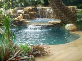 Tropical backyard pool waterfall into jacuzzi tropical