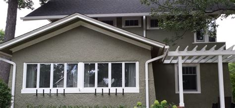 stucco prairie home newly painted with sherwin williams meadow trail and dover white trim