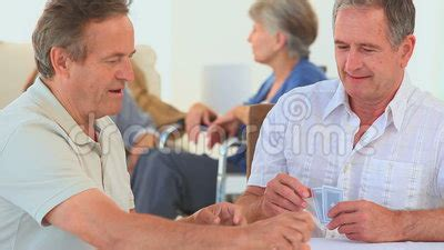 a of cards between two elderly friends stock footage