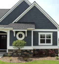 Cottage Grove Cape Cod - dark blue grey vinyl siding on a house with stone veneer around perimeter white trim black roof