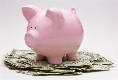 pink piggy bank with money pink piggy bank on top of a pile of one dollar bills