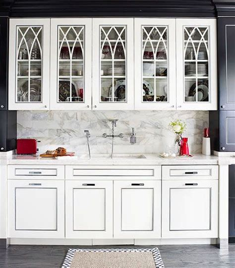 white kitchen cabinets with arch glass front doors