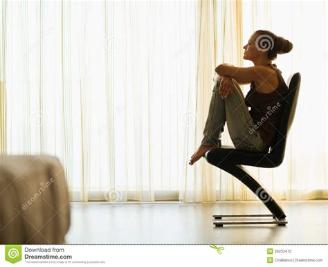 sitting window sitting on modern chair near window stock photo image 26233472