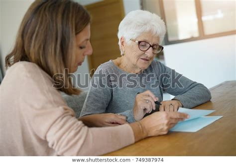 home assistant helping elderly woman paper stock photo