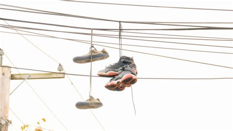 hang photos from wire sneakers hanging from telephone wire in the city is a