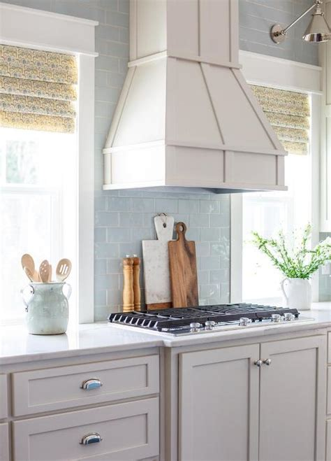 light blue glass subway tile backsplash blue kitchen island with wood and iron barstools