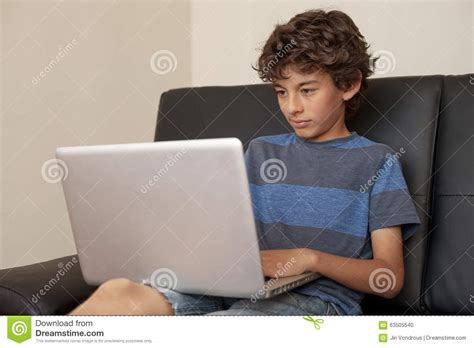 boy on couch latino boy sitting on sofa with laptop computer stock