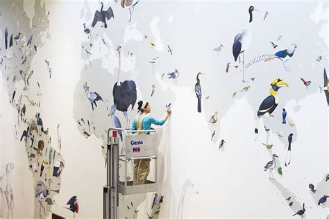 jane kim paints a giant mural at the cornell lab of
