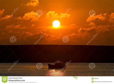 small fishing boat making small fishing boat on its way out to sea at sunset royalty