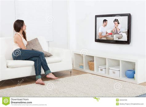 you sitting on the couch watching tv woman watching television while sitting on sofa stock