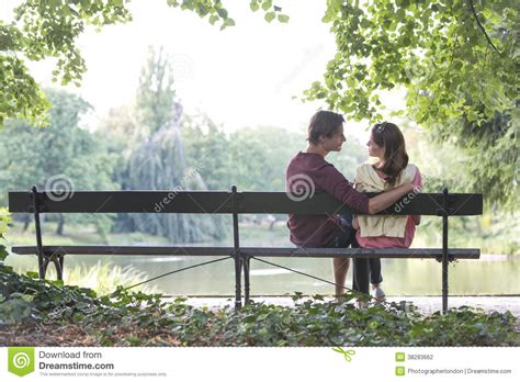 couple on park bench romantic young couple sitting on park bench by lake stock