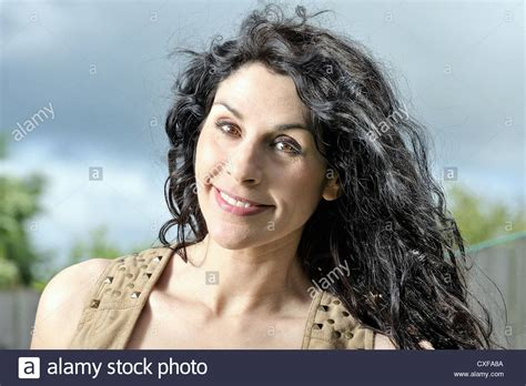 frizzy aged hair middle aged woman with black curly hair smiling and