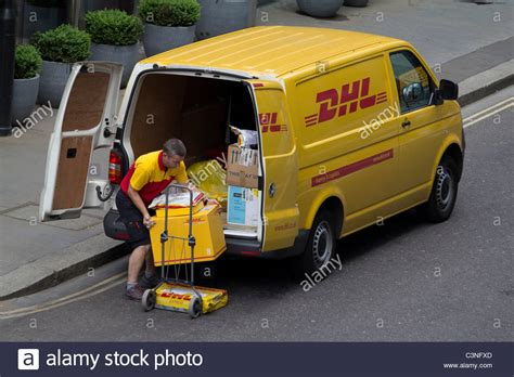 dhl delivery driver unloading van in city of london stock