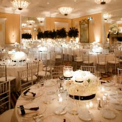 Real weddings low white floral centrepieces and candles decorate