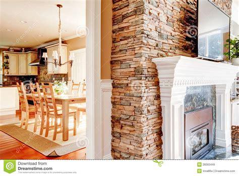 camini passanti camino di pietra con la tv e sala da pranzo e cucina