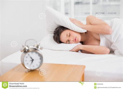 bed clock woman covering ears with pillow in bed and alarm clock on