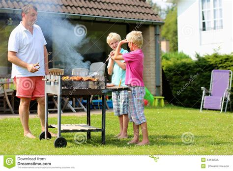 the backyard boys father with sons grilling meat in the garden stock photo