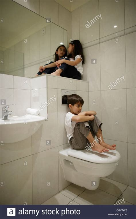 girl with boy in bathroom boy and girl sitting in bathroom stock photo royalty free