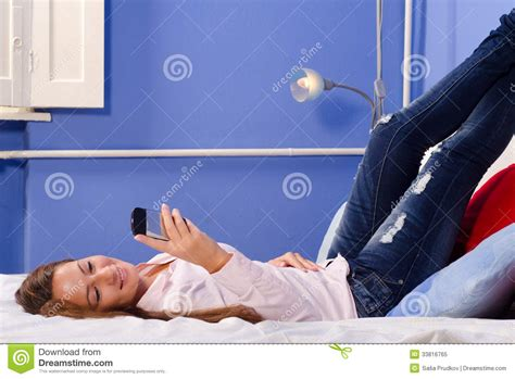 phone in bed smiling girl using mobile phone in bed royalty free stock