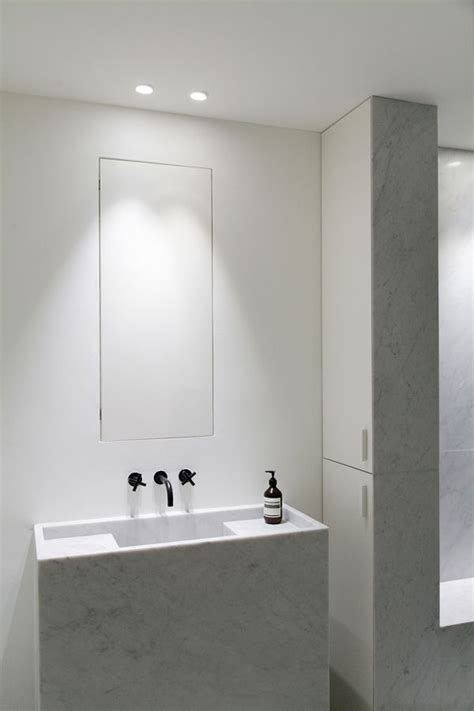 minimal bathroom carrara marble sink hidden mirror cabinet bold black