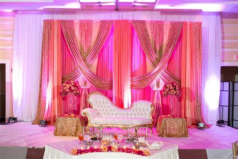 Glowing Reception Stage  coral, pink, and gold drapes #