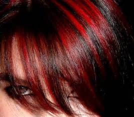 Lustrous black hair fashioned with red streaks on soft forehead bang