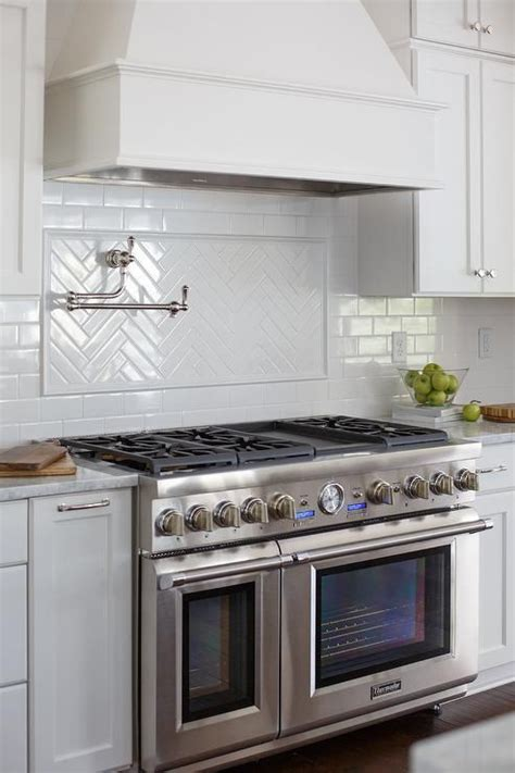 White wood kitchen hood over large stainless stove connected directly with white tile backsplash