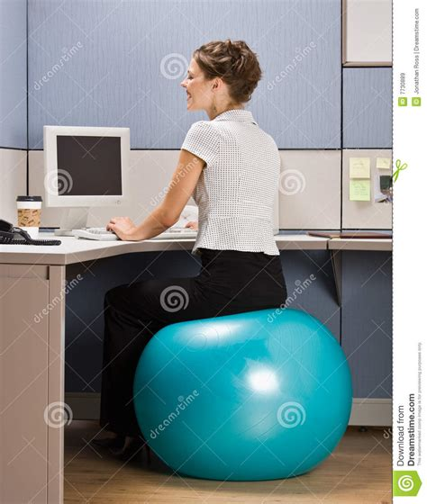 sitting on exercise ball at desk businesswoman sitting on exercise ball at desk royalty