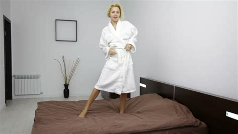 girl undressing in bedroom woman in white bathrobe comes to bedroom and wipe her hair