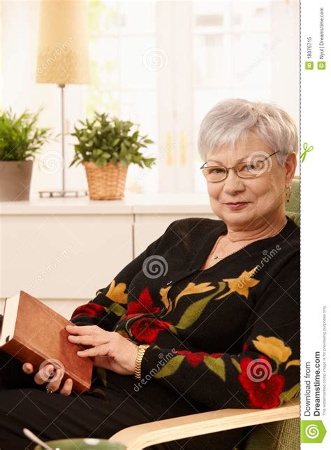 woman in armchair elderly woman in armchair with book royalty free stock