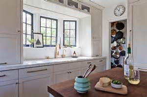 White porcelain sink and brass gooseneck faucet under a bay window
