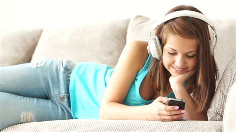 music on the couch young woman lying on couch with phone and listening to