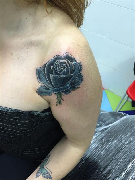 tatuaje de una rosa negra en el hombro de una chica