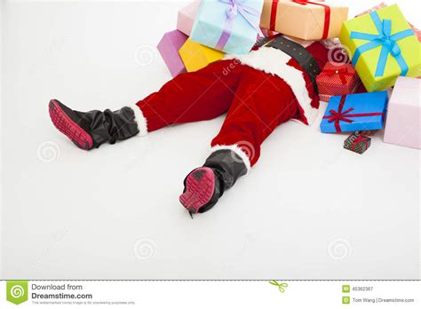 santa claus tired to lie on floor with many gift boxes