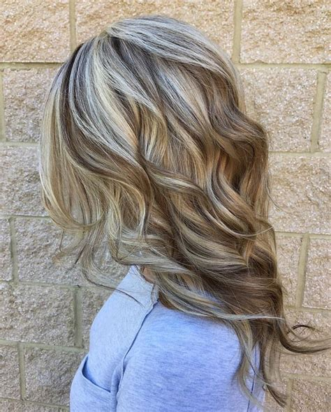 brown curly hair with low lights cool blonde highlight with rich lowlights mixed throughout
