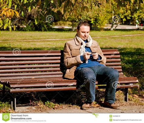 bench manly young man with a mobile phone stock photos image 34398573