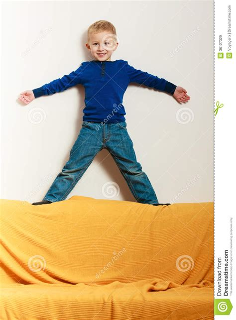 standing on the couch boy child kid preschooler standing on back rest of sofa