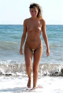 girl with brown curly hair and topless coming out of the water at the