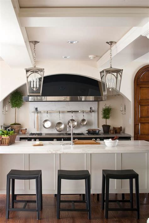 large scale nickel lanterns over the kitchen island not