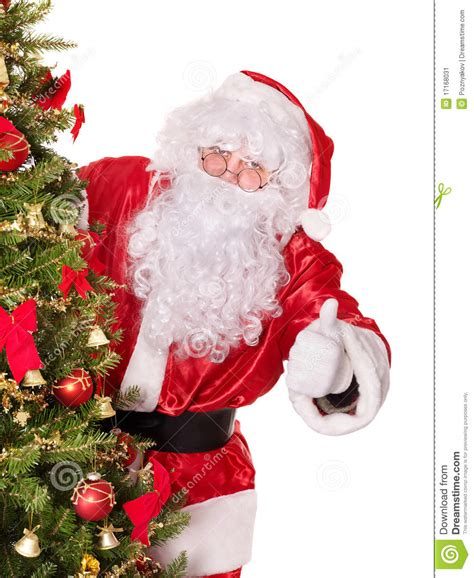 santa claus by christmas tree thumb up stock image