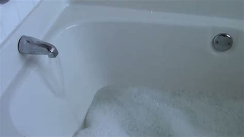 bathtubs and sinks have for the water to go down bathtub filling with water and soap suds stock footage
