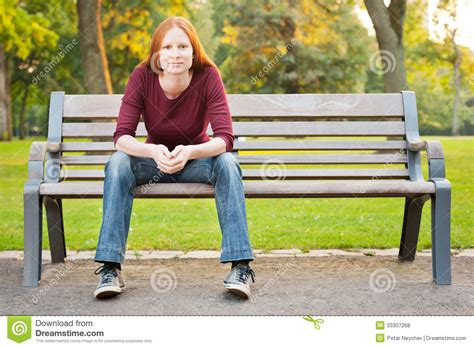 woman on bench a woman waiting on a bench in a park royalty free stock