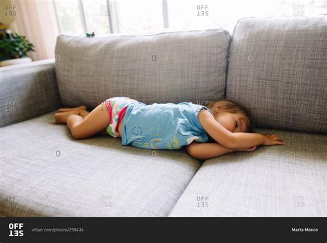 sleeping on the sofa toddler girl sprawled out sleeping on sofa stock photo